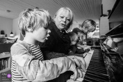 Zuid Holland family photojournalist captured this black and white photo of three boys practicing piano with their teacher
