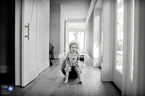 This black and white documentary family photo of a toddler bouncing down the hallway on a ball while her hair flies around her was captured by a Key West family photographer