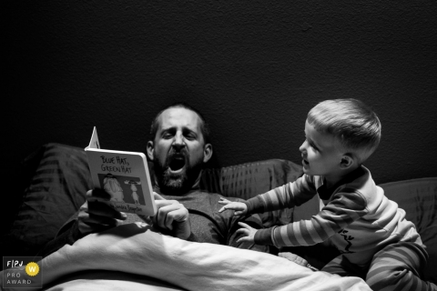 Washington family photographer captured a father yawning while reading his son a bedtime story in this documentary family photograph