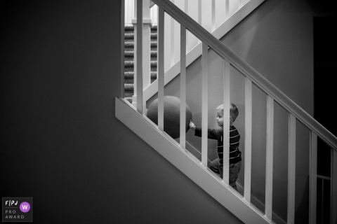 This black and white photo of a toddler playing with a balloon on the stairs was captured by a Washington documentary family photographer