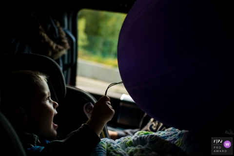 Washington family photojournalist captured this photo of a toddler in a car seat clutching happily to a big, purple balloon.