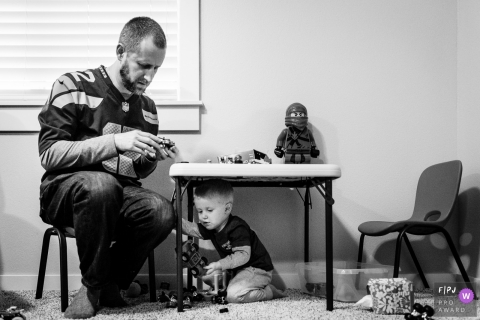 This black and white photo of a father patiently putting together Legos while sitting a child-sized table with his son playing underneath was captured by a Washington family documentary photographer