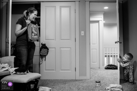 Washington family photojournalist captured this black and white photo of a mom trying to convince her toddler to get dressed while he playfully hides behind a door
