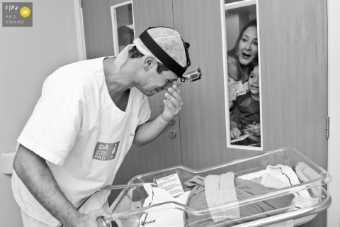 This black and white photo of a new dad crying tears of joy below his head-mounted GoPro camera as he shows off his newborn through a hospital window to waiting family was captured by a Rio de Janeiro birth photographer