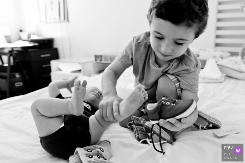 Rio de Janeiro family photojournalist captured this black and white photo of a big brother being a helper by trying to put on his baby siblings shoes