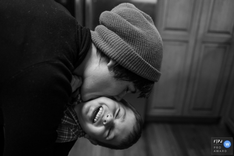 Brooklyn family photographer captured this black and white photo of a smiling young boy getting a big kiss on the cheek