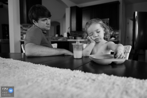 A toddler who is bored with lunch while dad waits nearby was captured at their kitchen table by an Atlanta Georgia documentary family photographer