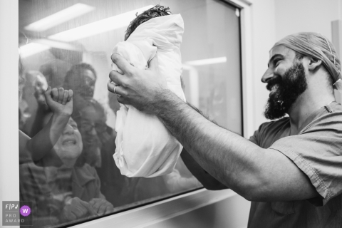 This black and white photo of a proud dad holding up his newborn for visitors to see was captured by a São Paulo birth photographer