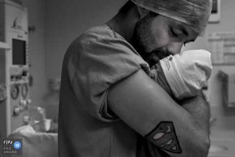 São Paulo Brazil birthing photo showing dad with Superman tattoo holding his new baby in the delivery room of the hospital.