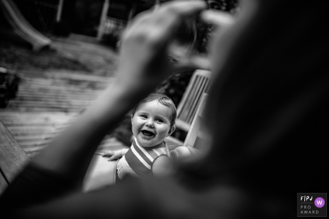 Black and white photo of a baby smiling on a bench outside taken through the crook of his mother's arm by a Lyon family photojournalist.