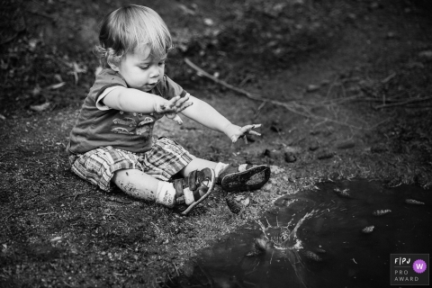 A boy tosses a rock into water in this black and white photo by a Lyon family photojournalist.