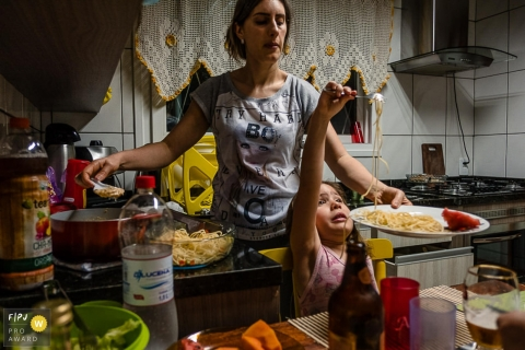 A little girl twirls spaghetti on her fork as her mother sets the plate down in this photo by a Rio Grande do Sul family photojournalist.