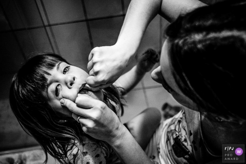 A mother helps her daughter floss in this black and white photo by a Rio Grande do Sul family photojournalist.