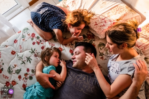 Two young girls sit on a bed with their parents in this photo by a Rio Grande do Sul, Brazil family photojournalist.