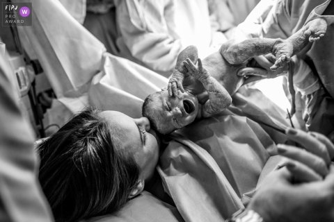 A woman holds her newborn infant for the first time after giving birth in this black and white photo by a Rio de Janeiro, Brazil birth photographer.