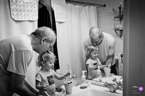 A grandfather kisses the top of his granddaughter's head as she gets ready to brush her teeth in this black and white photo by a Washington, D.C. family photojournalist.