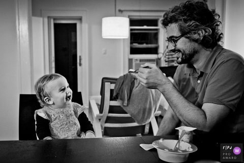 A baby girl smiles as her father gets ready to feed her in this black and white photo by a Washington, D.C. family photojournalist.