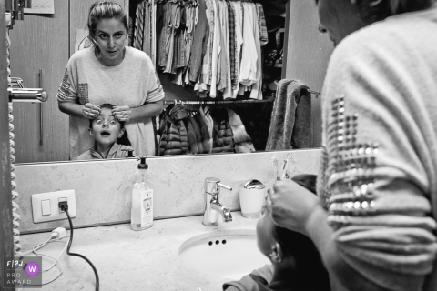 A mother gets ready to do her son's hair as he makes a face in the mirror in this black and white photo by a Washington, D.C. family photojournalist.