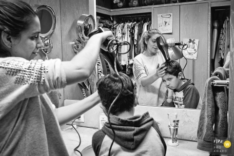 A boy is not happy about his mother blow-drying his hair in this black and white photo by a Washington, D.C. wedding photographer.
