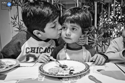 A boy kisses his younger brother during dinner in this black and white photo by a Washington, D.C. family photojournalist.