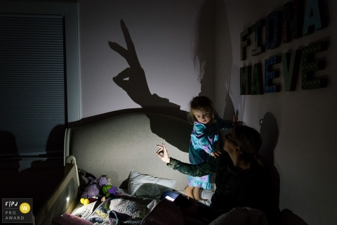 A young girl watches her mother make shadow puppets in this photo by a Washington, D.C. family photojournalist.