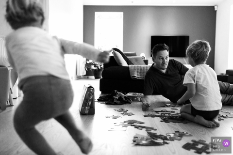 Black and white family photo of a father putting a puzzle together with his son as another young boy runs past, by a Denmark family photojournalist.