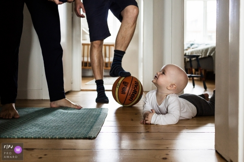 Family photo of a baby laying on the floor looking up at the parents as the father stands with his foot on a basketball, by a Denmark family photojournalist.