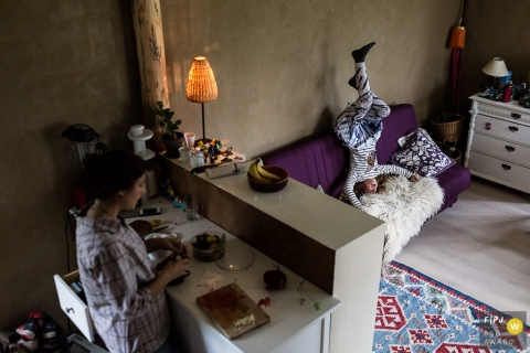 Family photograph of a girl doing a head stand on a couch as her mother prepares food in the kitchen by a Denmark family photojournalist.