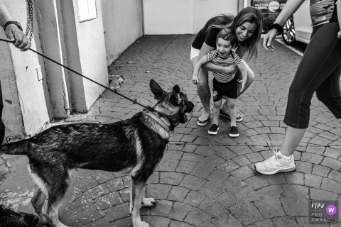 A mother holds her son back from as he tries to approach a dog in this black and white photo by a Sao Paulo family photojournalist.