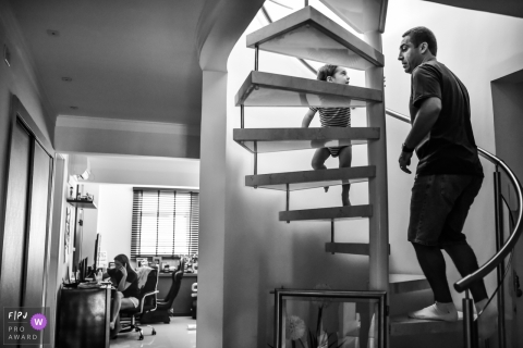 Black and white family photo of a father on a spiral staircase with a young boy by a Sao Paulo family photojournalist.