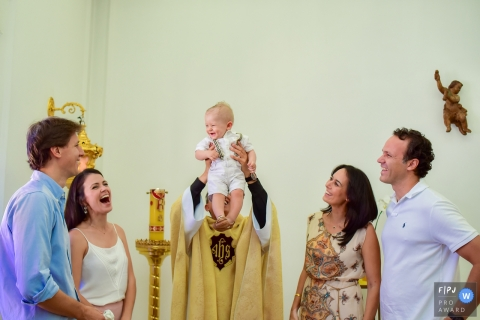 Family photo of a priest holding up a smiling baby as the parents and godparents smile back by a Sao Paulo family photojournalist.