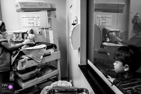Black and white photo of a nurse with a newborn baby in the hospital as a young boy watches through the window by a Minas Gerais, Brazil documentary birth photographer.