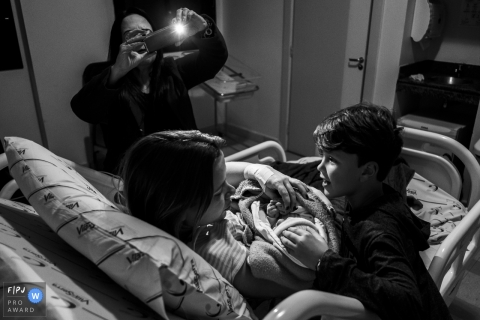Black and white photo of a boy meeting his new sibling in the hospital as a woman takes a photo of them. Awarded image by a Minas Gerais, Brazil birth photographer.