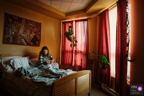 Family photo of a mother sitting in bed with her baby by a Montreal, Quebec family photojournalist.