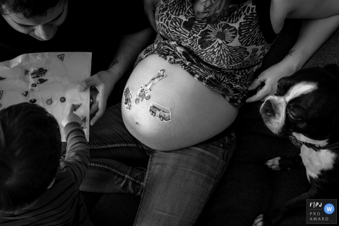 Black and white family photo of a father helping a young boy put stickers on his mom's pregnant belly by a Montreal, Quebec birth photographer.