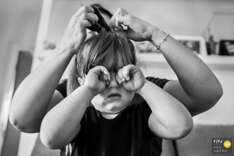 A little girl rubs her eyes as her mom helps her with her hair behind her in this black and white photo by a Minas Gerais family photojournalist.
