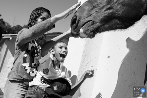 Black and white family photo of two children petting a horse by a Minas Gerais family photojournalist.