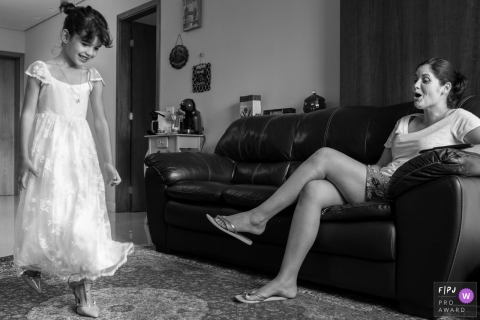 Black and white family photo of a mother watching her young daughter walk in high heels by a Minas Gerais family photojournalist.