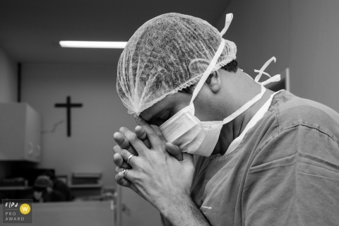 Black and white photo of a man wearing a cap and mask bending his head to his folded hands in the hospital by a Rio de Janeiro, Brazil birth photographer.