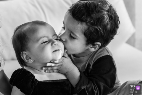 Black and white family image of a young boy kissing his baby sister - photo by a Rio de Janeiro, Brazil family photographer.