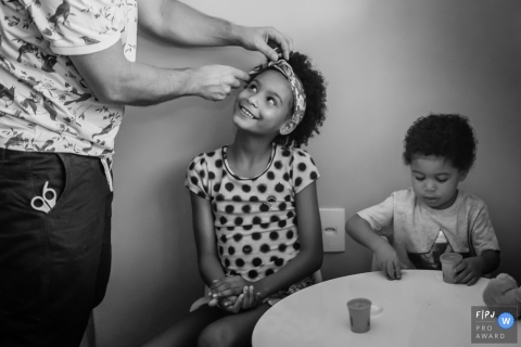 Black and white family photo of a man helping a young girl with her hair by a Minas Gerais, Brazil family photojournalist.