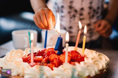 Un enfant allume une bougie en forme de «4» sur une tarte aux fraises dans cette image primée du FPJA, capturée par un photographe de famille du Gelderland, aux Pays-Bas.