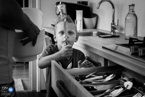 Un petit garçon regarde un couteau à beurre sur cette image créée par un photographe de famille d'Amsterdam.