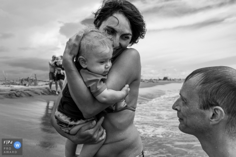 A mother holds her little boy on the beach in this photograph created by a Modena family photojournalist.