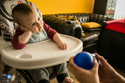 A little boy leans his head against his hand after lunch in his high chair  in this FPJA award-winning picture by a Minas Gerais family photographer.