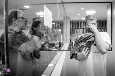 A father gets emotional as he holds up his newborn for his family to see in the hospital in this black and white photo by a documentary-style Rio de Janeiro, Brazil birth photographer.