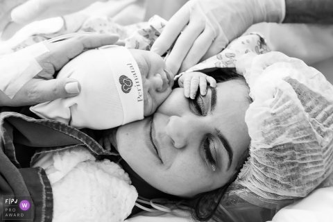 A mother cries as she holds her infant for the first time in the hospital in this black and white image created by an award-winning Rio de Janeiro, Brazil birth photographer.