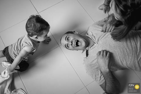 Un petit garçon joue avec son père qui repose par terre sur cette photo d'un photographe de famille documentaire de Sao Paulo, Brésil.