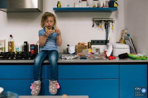 Une petite fille assise sur le comptoir de la cuisine en train de manger son sandwich dans cette image primée du FPJA, capturée par un photographe de famille de Zuid Hollands, aux Pays-Bas.