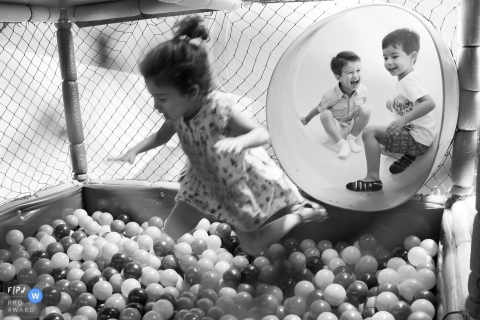 A little girl jumps into a ball pit while her brothers wait in the tunnel behind her in this image created by a Sao Paulo family photographer.